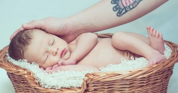 Biokleidung baby schlaeft in korb wird gestreichelt
